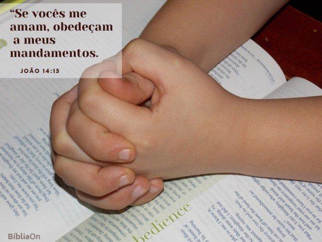 Criança - mãos entrelaçadas em oração sobre bíblia - João 14:15